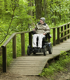 Man in wheelchair on boardwalk in forest