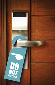 Photograph of a 'do not disturb' sign hanging on a wooden door.