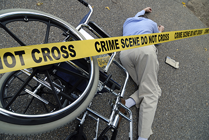 Crime scene tape by wheelchair and man lying on ground.