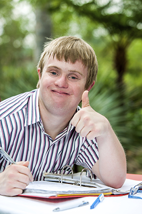 Young man with Down syndrome studying