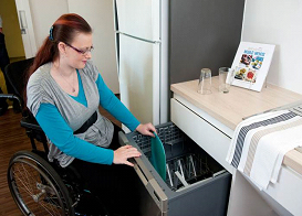 Woman in a wheelchair unpacking a dishwasher at home