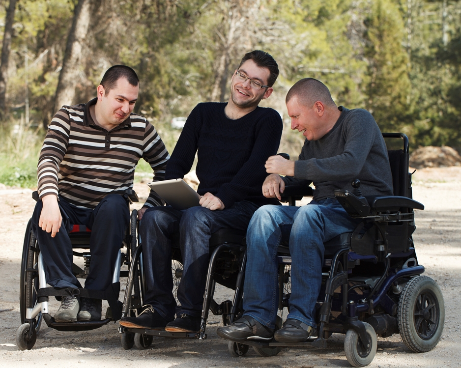 Three friends sit together, enjoying each other's company in the park. Each of them is in an electric wheelchair.