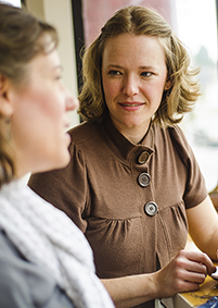 A friendly woman listens to another speaking.
